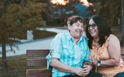senior mother and adult daughter sitting together on park bench talking